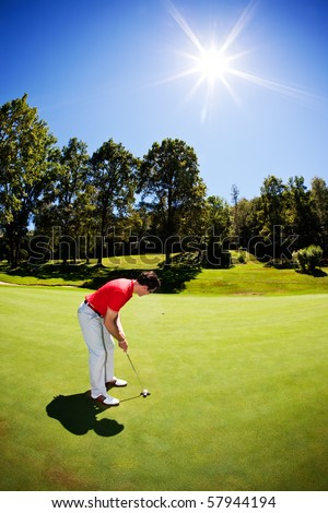 One young white male golfer, red shirt and white pants, goes for the green on the fairway. Vertical frame, clear summer day, back-light. - stock photo