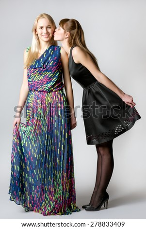 One young woman leaned forward to kiss another one - stock photo