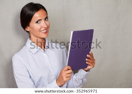 One young woman smiling and holding tablet with a toothy smile while looking at camera in button down shirt against grey texture background