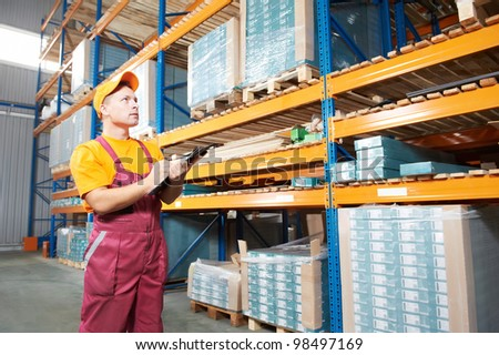 one young worker inspector man in uniform in front of warehouse rack arrangement stillages - stock photo