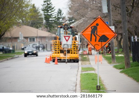 Ongoing road construction work, orange signs and traffic cones alerting motorists approaching the site and the construction crew. - stock photo