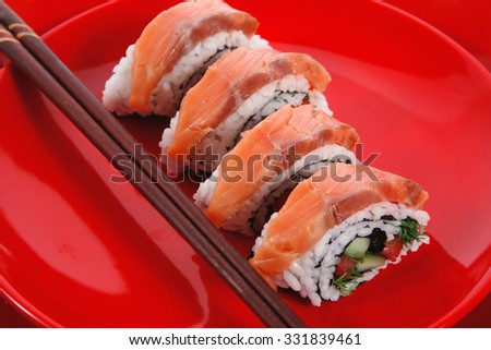 onigiri inside out sashimi shushi with raw salmon and sticks on red plate isolated over white background - stock photo