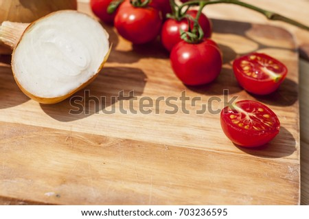 Onion and cherry tomato food composition on the wooden table