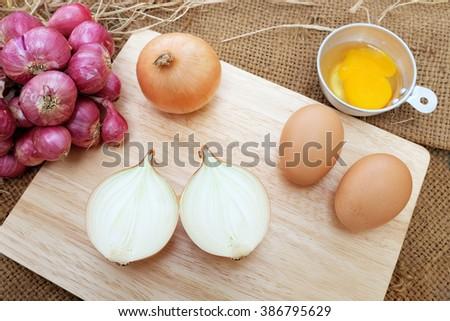onion and egg on wood block background - stock photo