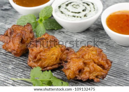 Onion Bhajis & Dips - Deep fried south asian snack with chili sauce, mint raita and mango chutney, garnished with mint and coriander leaves on a slate. - stock photo