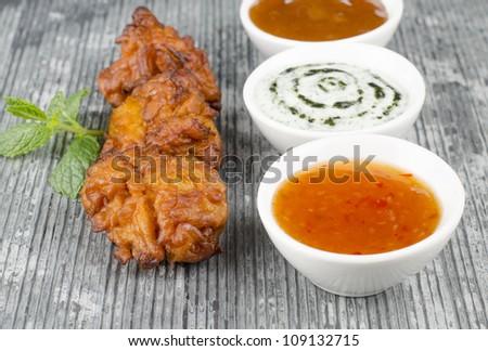 Onion Bhajis & Dips - Deep fried south asian snack with chili sauce, mint raita and mango chutney, garnished with mint leaves on a slate. - stock photo