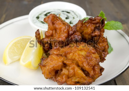 Onion Bhajis & Mint Raita - Deep fried south asian snack yoghurt and mint dip, garnished with mint leaves and lemon wedges on a white plate. - stock photo