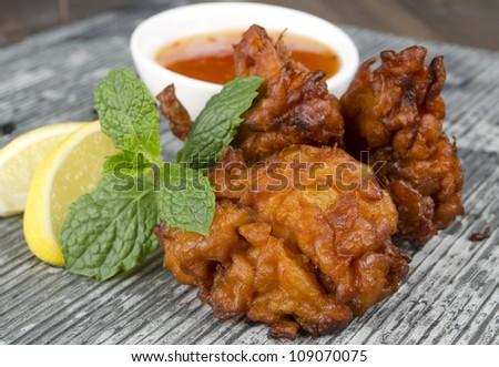 Onion Bhajis with mango chutney and lemon wedges garnished with mint leaves on a slate. - stock photo