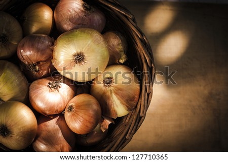 Onion in a basket on wood background - stock photo