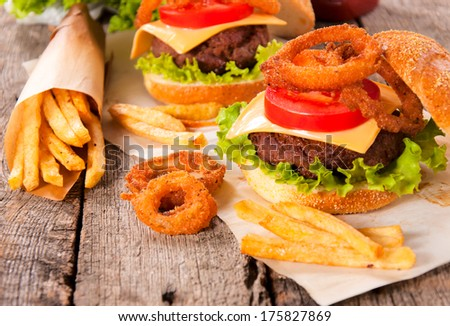 Onion rings,french fries and cheeseburger on the wooden table - stock photo