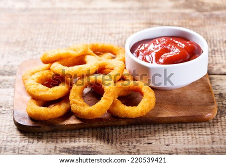 onion rings with ketchup on wooden board - stock photo