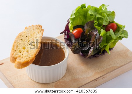 Onion soup in ceramic cup with toast and fresh vegetables on wood plate. Clean and healthy eating concept food. - stock photo