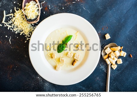 onion soup puree in a white plate with toasts and cheese on the black table - stock photo