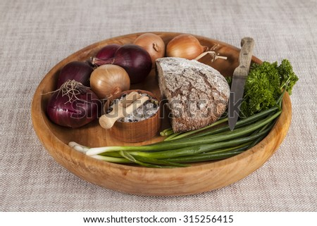 Onions, brown bread wooden tray with parsley and salt and celery ,knife. - stock photo