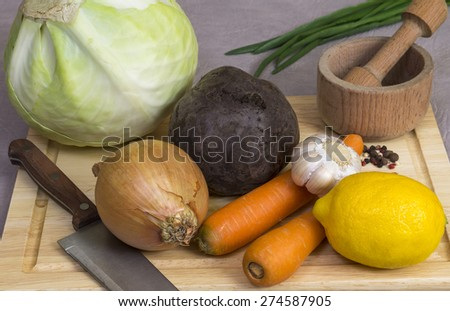 Onions, carrots, beets, cabbage, garlic and lemon on a chopping Board - stock photo