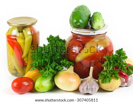 onions, garlic, cucumbers, tomatoes and parsley lie on a light surface. A row two banks with tinned vegetables