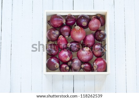 onions in wooden tray, white wood table background, top view - stock photo