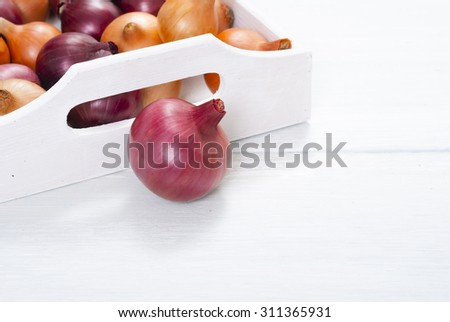 onions on white wood tray, wooden table background