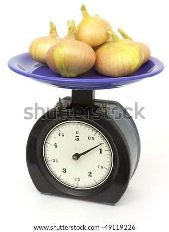 Onions weighing on old kitchen scales - stock photo