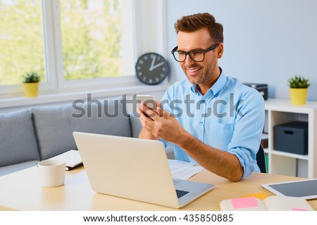 Online banking is easy with mobile app and phone - man paying bills with his smartphone - stock photo