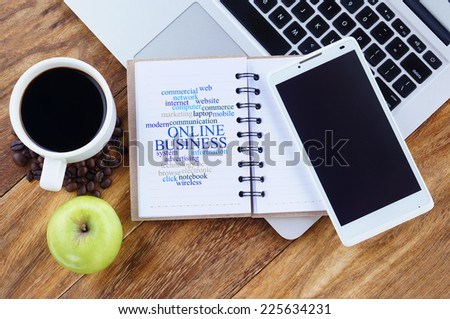 Online Business word cloud arrangement concept on smartphone screen. Notebook,smartphone,book, apple and a cup of coffee on wooden table.  - stock photo