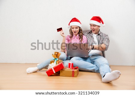 Online Christmas Shopping. Happy Smiling Couple Using Credit Card to Internet Shop. Young couple with laptop and credit card buying online. Christmas and New Year Gifts. e-shopping - stock photo