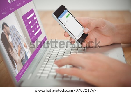 Online dating app against man holding mobile phone while typing on laptop at desk - stock photo