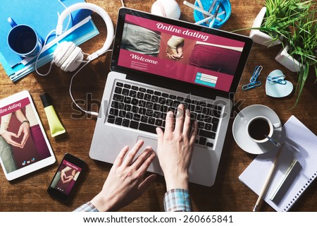 Online dating website on a laptop display, hardwood desktop and stationery on background - stock photo