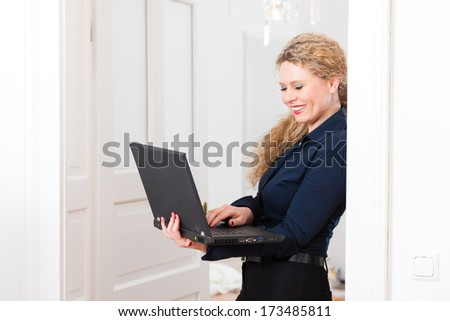 Online Dating - Young businesswoman at home while using a laptop computer, for dating or reading emails - stock photo