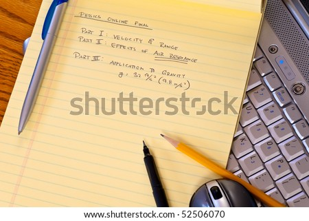 Online Exam Notes with Computer - stock photo