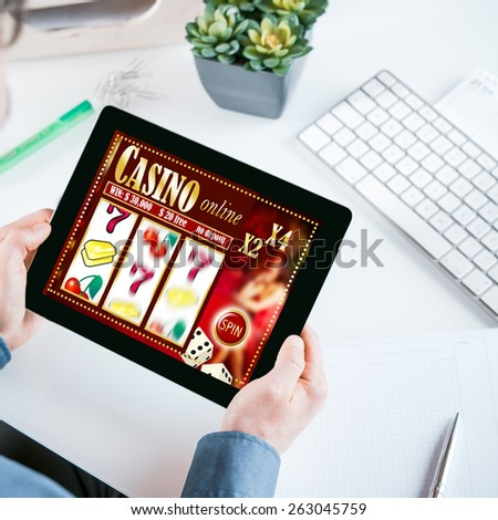 Online gambler gambling at the office holding his tablet computer showing a casino interface with lucky numbers above his desk and workspace - stock photo