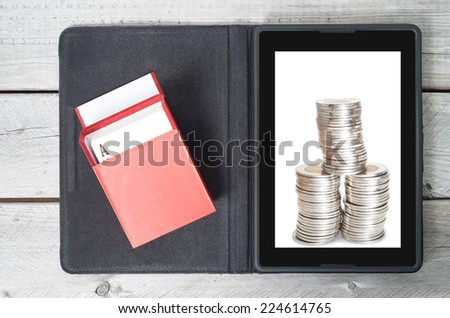 Online gambling concept with a tablet, red box of cards and  money - stock photo
