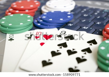 Online Gambling Hand of playing cards laid on computer keyboard with a selection of betting chips. this depicts the modern trend of gambling and playing cards online with competitors world wide. - stock photo