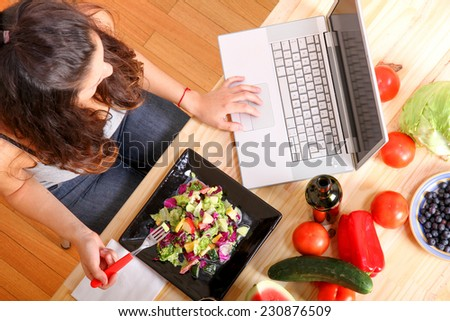 Online information for vegetarians. A young girl eating salad while using a Laptop. - stock photo