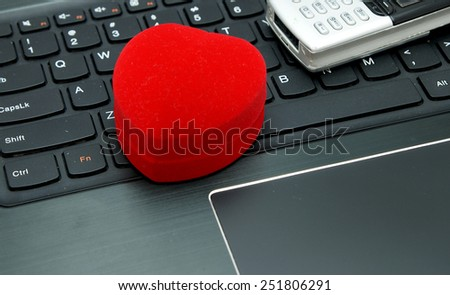 Online / Internet dating: Heart shape jewelery box on the notebook keyboard next to the cell (mobile) phone - stock photo