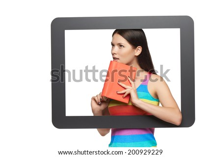 Online library concept. Pensive young woman with a book, standing behind tablet frame, over white background - stock photo