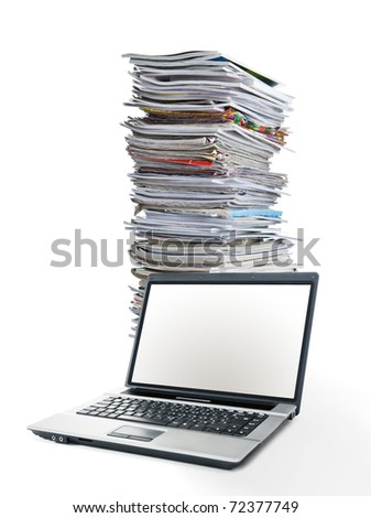 Online magazines -Stack of magazines next to a laptop - stock photo