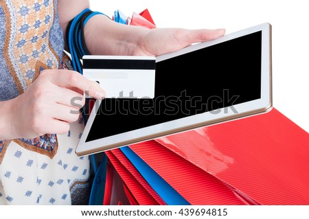 Online payment concept with digital tablet and debit card in close-up in young shopaholic hands isolated on white background - stock photo