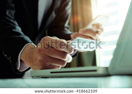 Online payment,Man's hands using smartphone laptop and holding credit card as Online shopping concept in morning light.