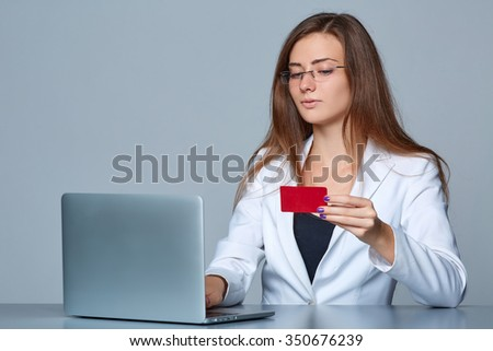 Online payment shopping concept. Thinking business woman sitting at table with laptop, holding empty credit card, looking away in thoughts, isolated on  gray background. - stock photo