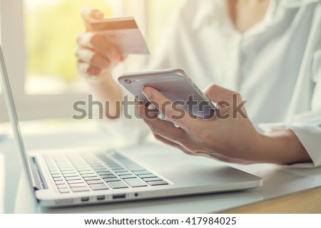 Online payment,Woman's hands holding a credit card and using smart phone for online shopping - stock photo