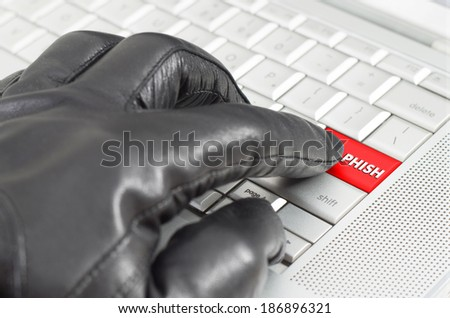 Online phishing concept with hand wearing black glove  - stock photo