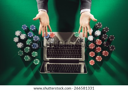 Online player's hands palms up with laptop and stack of chips all around on green table top view - stock photo