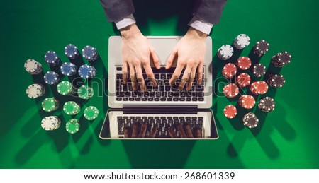 Online player's hands with laptop and stack of chips all around on green table top view, he is typing on the keyboard - stock photo