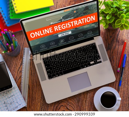 Online Registration Concept. Modern Laptop and Different Office Supply on Wooden Desktop background. - stock photo