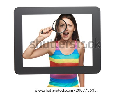 Online search concept. Surprised young woman looking through magnifying glass at camera, standing behind tablet frame. - stock photo