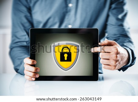 Online security concept with a man holding a tablet computer pointing to the screen displaying a yellow shield and padlock icon - stock photo