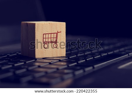 Online shopping and e-commerce background with a wooden cube showing a shopping cart icon resting on a computer keyboard viewed low angle over black with copyspace. - stock photo