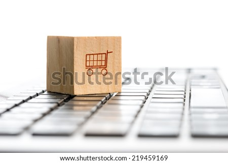 Online shopping and e-commerce concept with a wooden block with an icon of a shopping cart standing on a computer keyboard, viewed low angle with copyspace. - stock photo