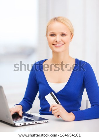 online shopping and technology concept - smiling young woman with laptop computer and credit card